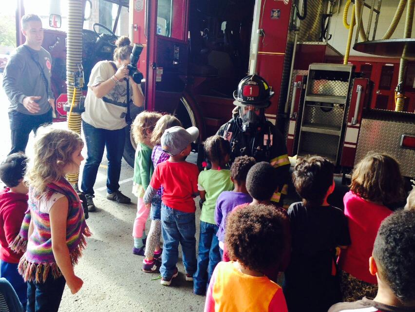 Firefighter showing firefighting equipment to children
